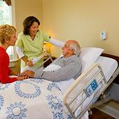 Older patient reclines in bed, talking with clinician and family member