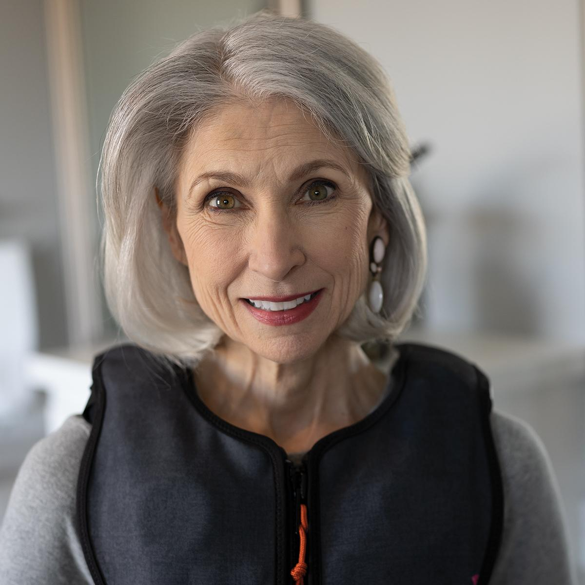 A woman with gray hair wears a fashionable, black Monarch® System vest with orange accents.
