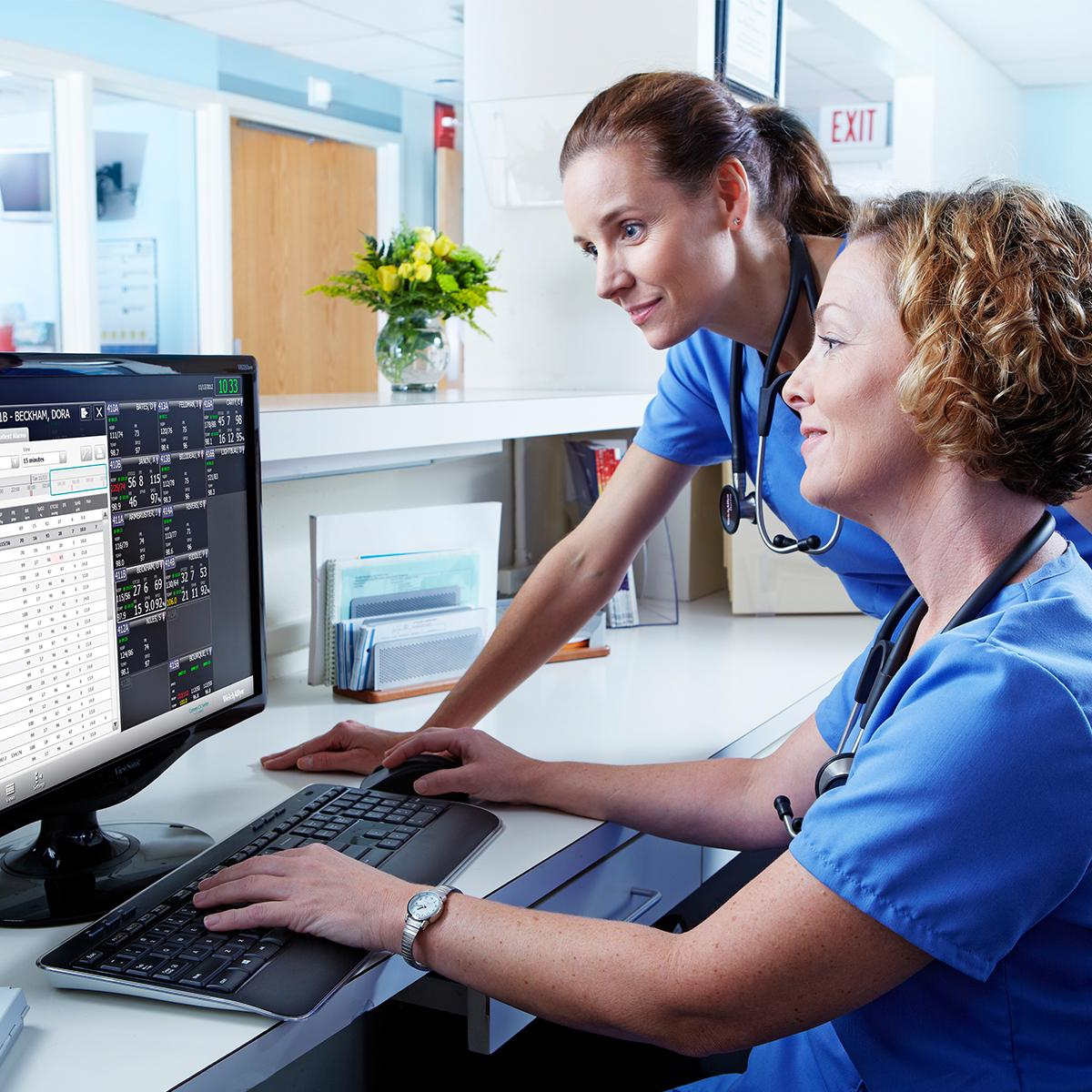 Two nurses looking at a desktop computer screen at a nurse's station reviewing patient statuses from the Connex Central Station software