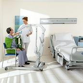 A patient sits in a seated sling attached to a patient lift while a clinician assists, with a Hillrom 900 bed in the room