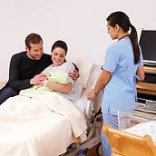 Smiling new parents hold their newborn baby in an Affinity 4 Birthing Bed, caregiver at their side