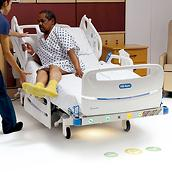 Female hospital clinician helps male patient exit the Centrella Smart+ Bed