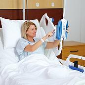 Une patiente souriante utilise la console de communication du lit Centrella<sup>®</sup>Smart+