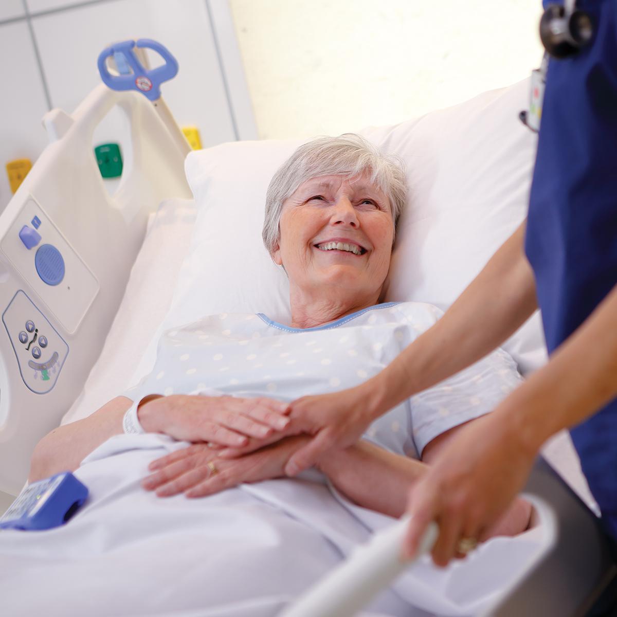 Une patiente âgée dans le lit CentrellaSmart+ rit avec un clinicien
