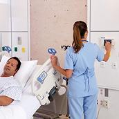 Nurse interacting with a wall-mounted screen next to a patient