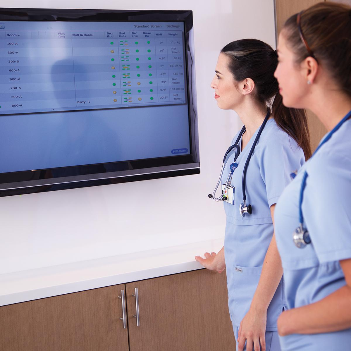 Two nurses looking at a large wall-mounted screen