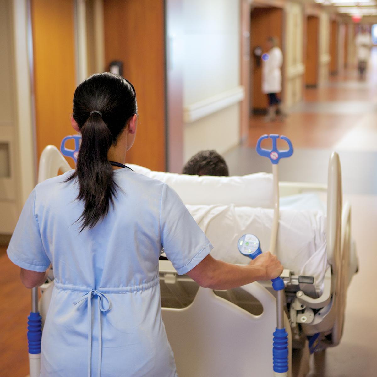 Una vista por encima del hombro de un cuidador que transporta una cama bariátrica Compella por un pasillo de hospital.