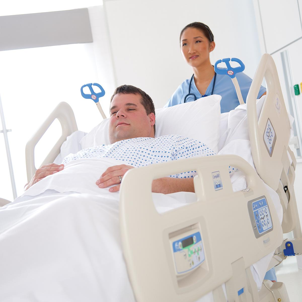 Une soignante détendue ne se fatigue pas en poussant un lit bariatrique Compella, dans lequel un patient est incliné confortablement.
