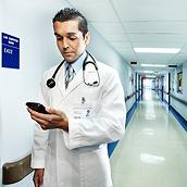 Clinician looking at smartphone in hospital hallway