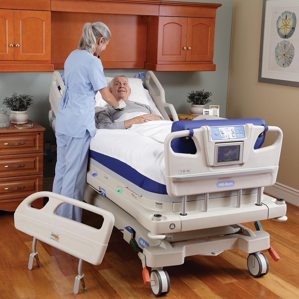 An over-the-shoulder view of a healthcare provider checking on her smiling patient as he recovers in an Envella therapy bed.