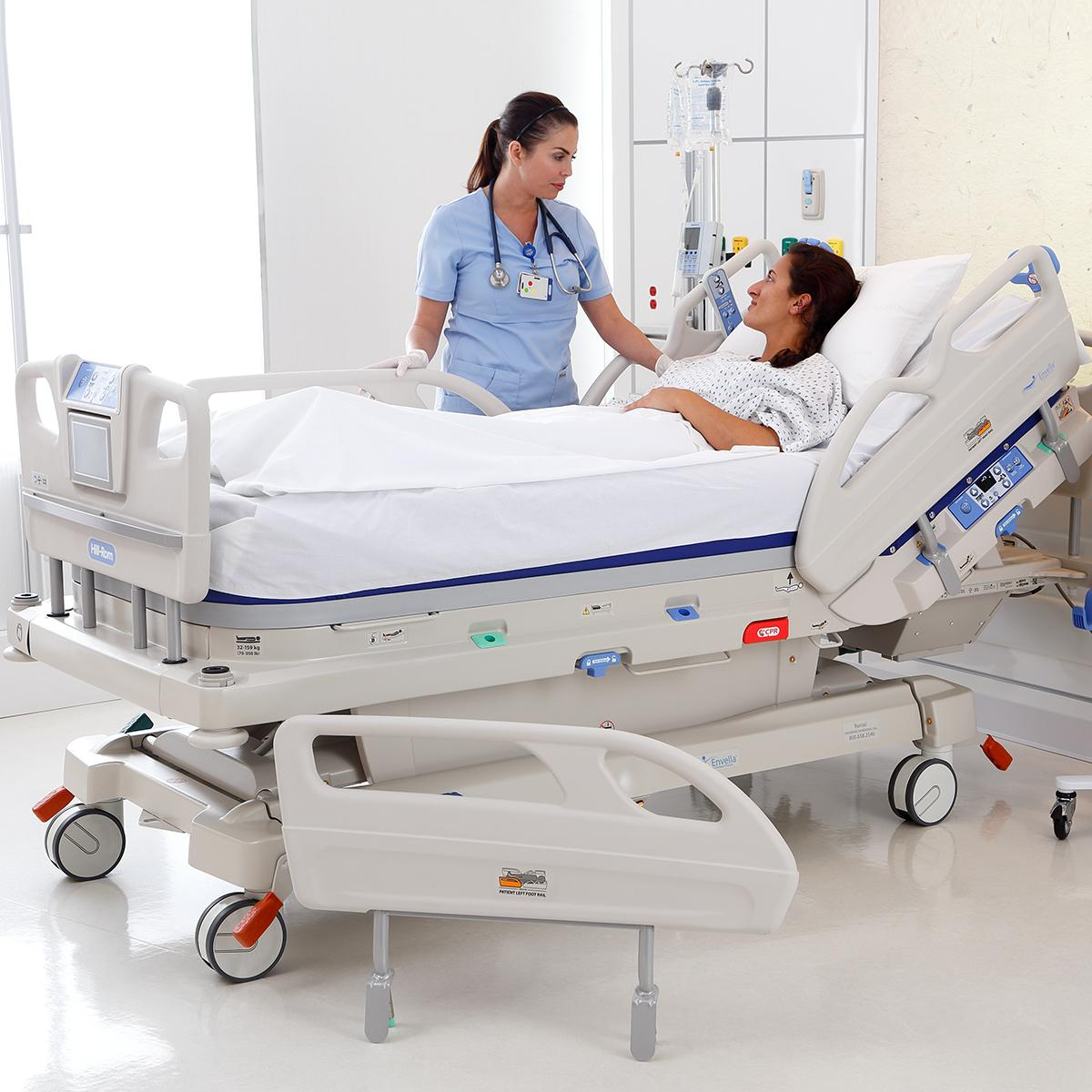 A hospital nurse speaks with her recovering wound care patient, who is lying in an Envella bed. The bed's siderails are down.