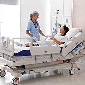 A clinician checks on her patient, who is recovering in an Envella therapy bed in a clean hospital room.