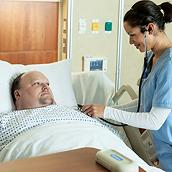 Bariatric patient lies in Excel Care ES Bariatric Hospital Bed while a clinician listens to his heart with a stethoscope