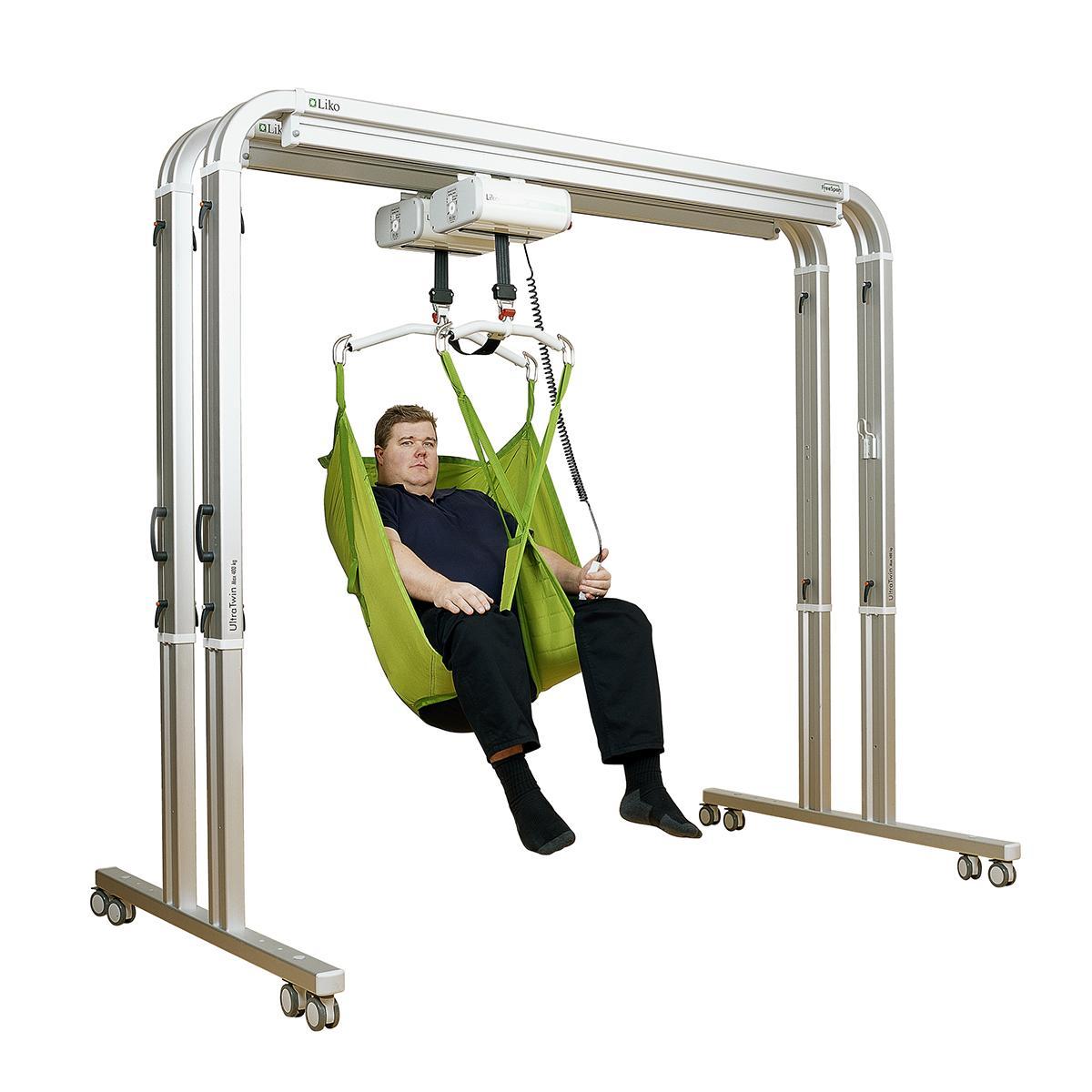 Un homme s'assoit dans un harnais vert dans un système de levage UltraTwin FreeSpan de Hillrom.