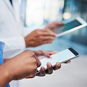 A clinician in blue scrubs and a physician in a lab coat send and receive information on their smartphones