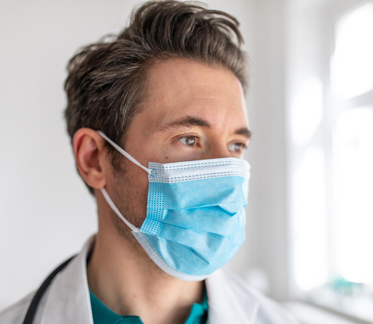 A hospital clinician wearing a mask is deep in thought