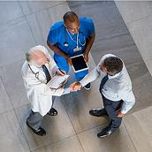 Clinician in blue scrubs with a tablet and physician in white lab coat, speaking to a man in business attire