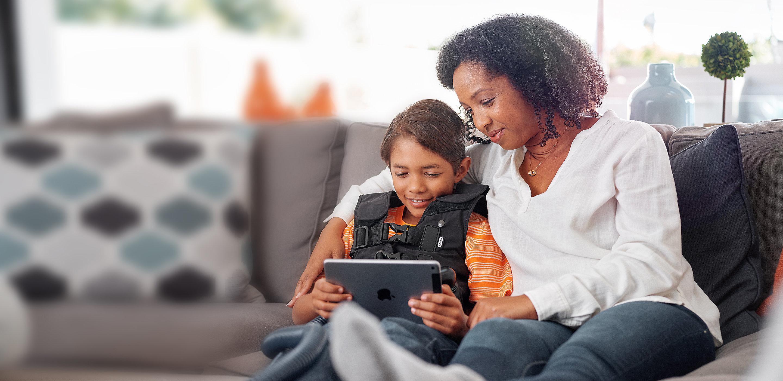 Una mamá y su hijo descansan en el sofá de su casa. El niño recibe tratamiento respiratorio con un dispositivo de Hillrom.