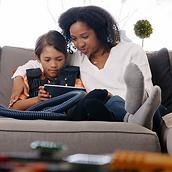 In this video clip, a young child uses The Vest System at home while using a tablet with his mother.