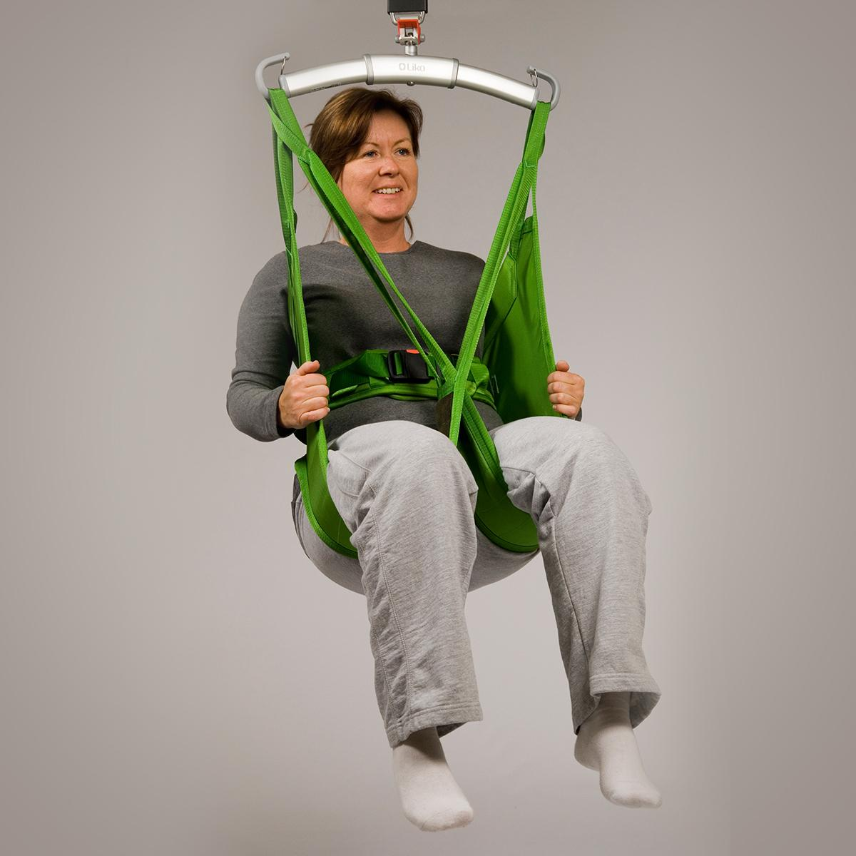 A patient in a seated position smiles in a Hillrom Hygiene sling