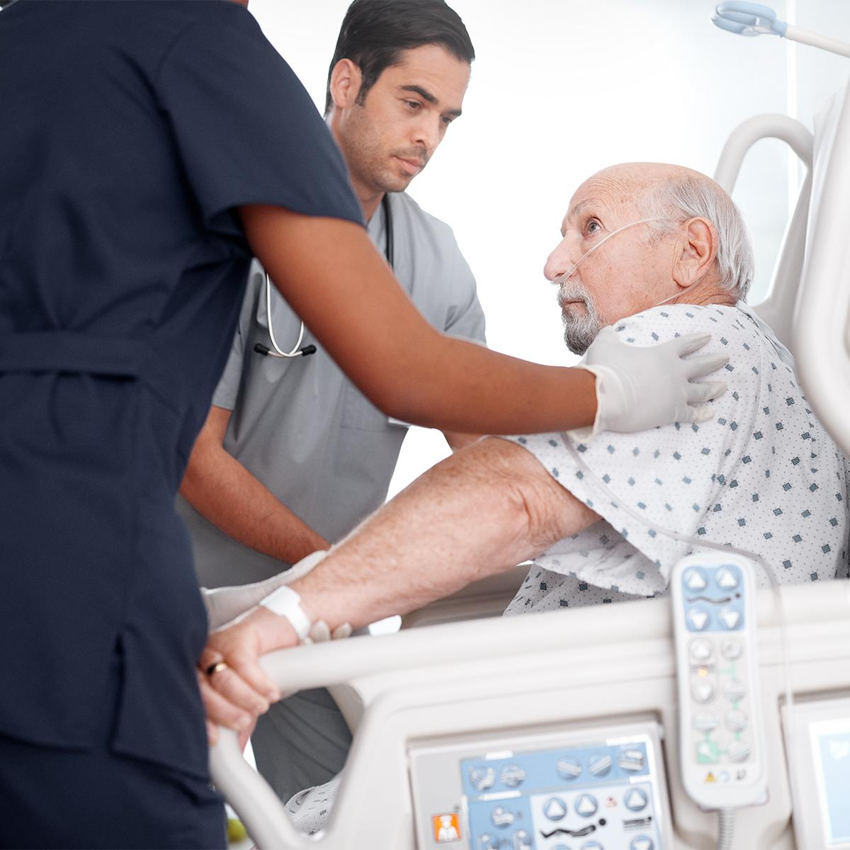 Two clinicians attending to an older patient sitting up in a hospital bed
