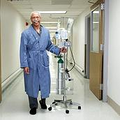 Smiling respiratory patient wearing nasal canula and walking in hospital hallway with Life2000 Ventilator and oxygen tank.