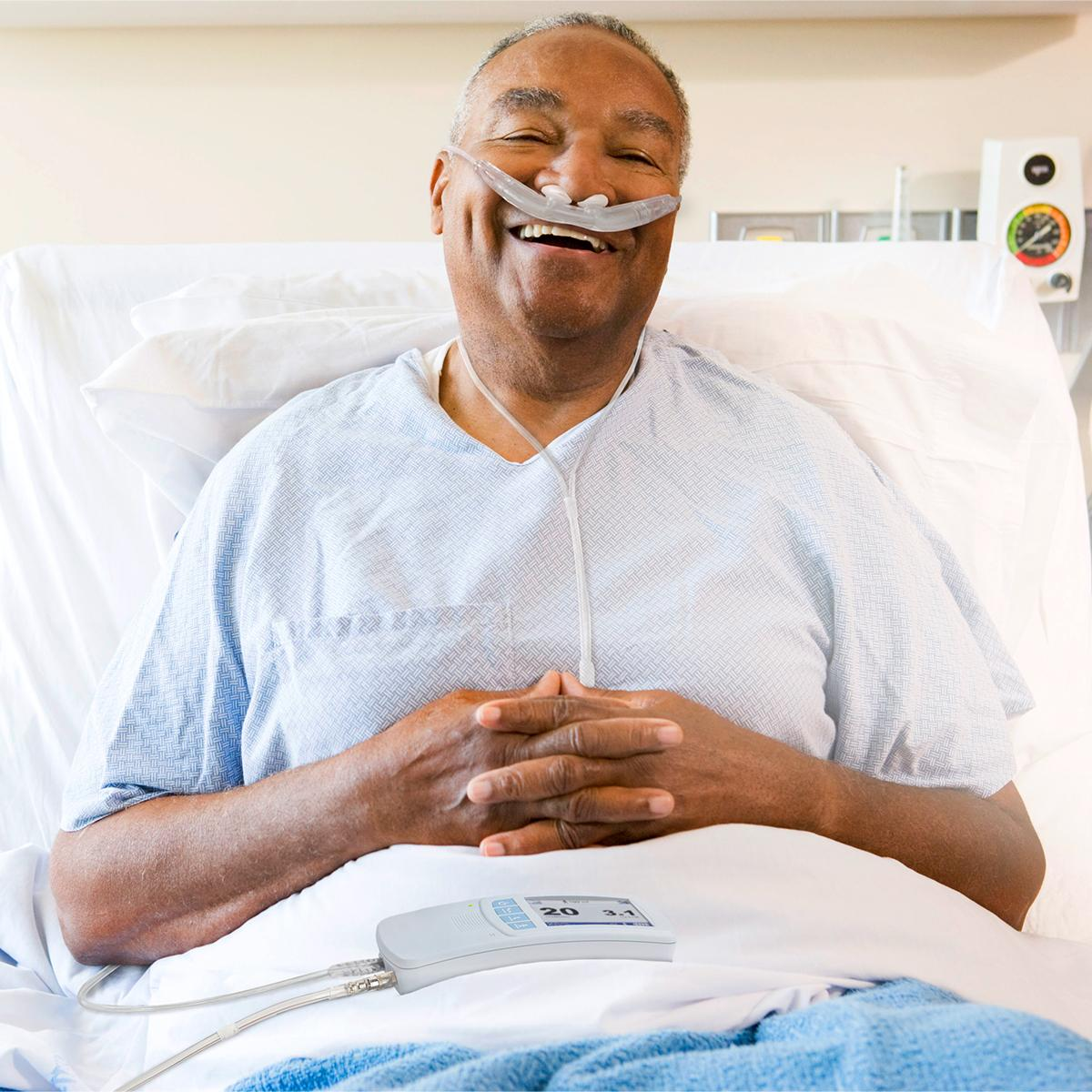 Smiling patient with Hillrom Life2000 mobile ventilator talking with doctor or respiratory therapist in hospital hallway.