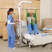 A patient is lifted above a hospital bed by a Golvo Mobile Lift operated by a clinician
