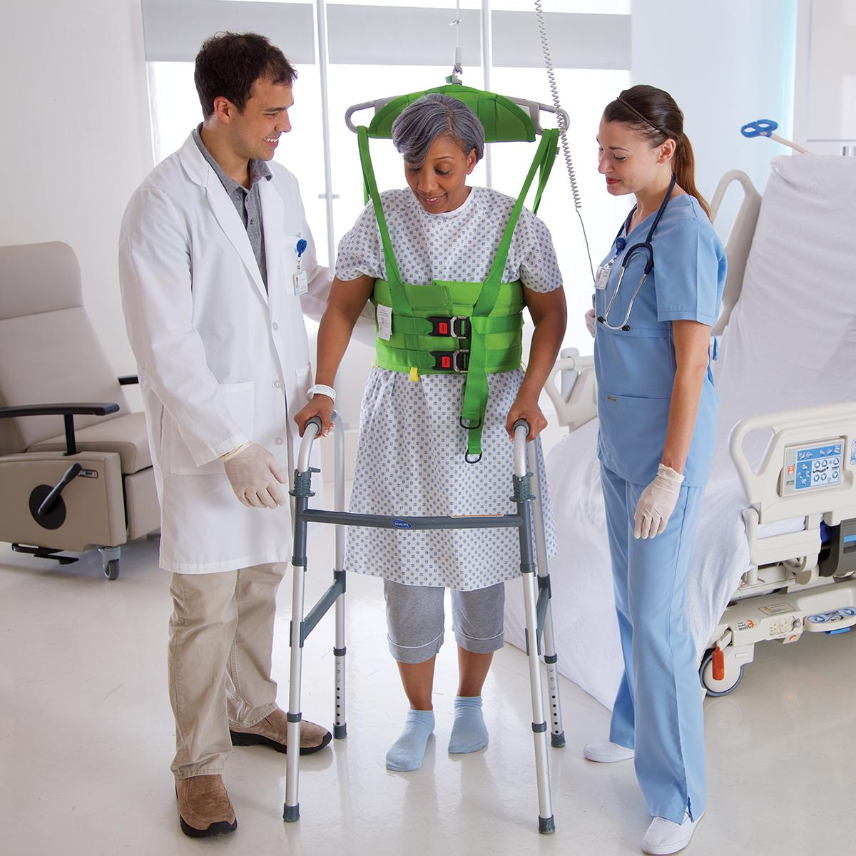 An overhead lift attached to a green vest supports a female patient using a walker, with two clinicians helping