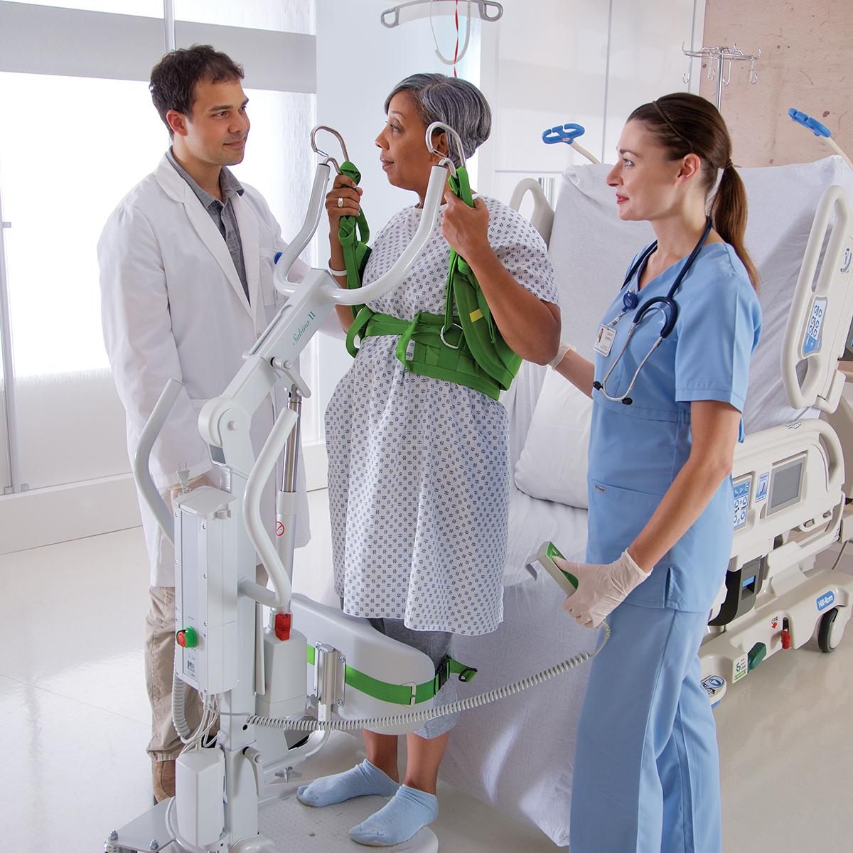 Two clinicians help an older female patient stand in a hospital room using a Sabina II mobile lift