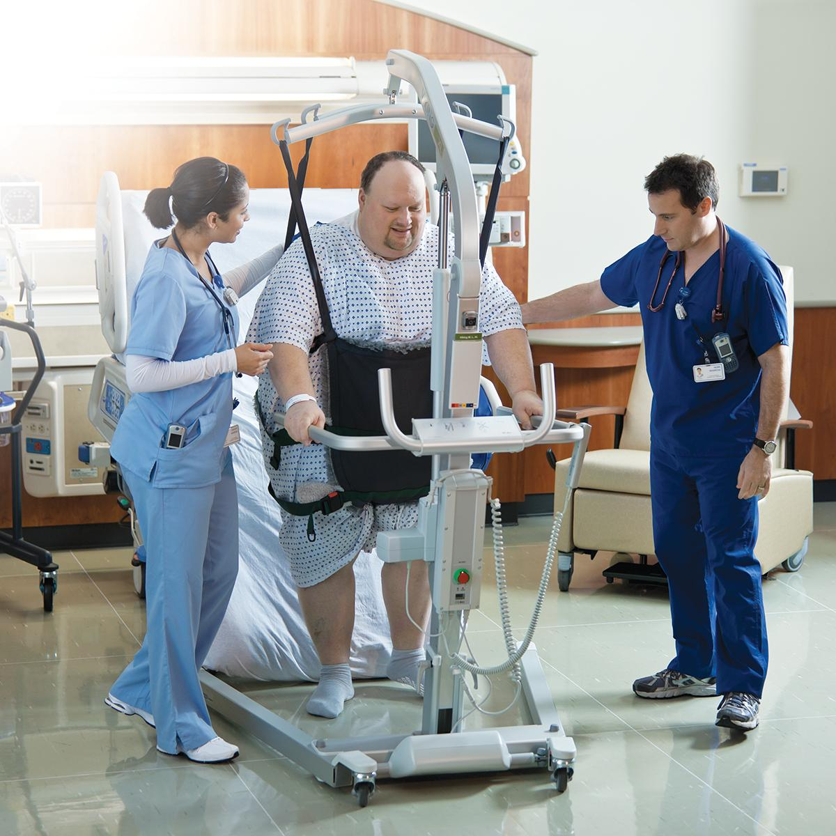 A patient is safely supported by his clinicians and a Viking XL mobile lift while exiting a TotalCare Bariatric Plus Hospital Bed.