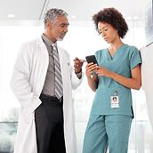 Two clinicians consult in a hospital hallway. One clinician holds her smartphone. Her male colleague points to its screen.