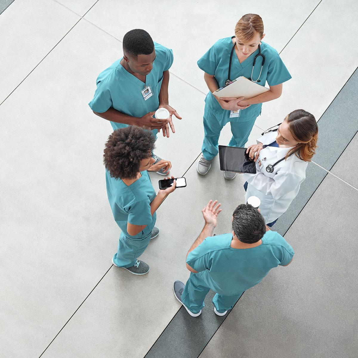 Overhead view of four nurses and a clinician conversing in a circle