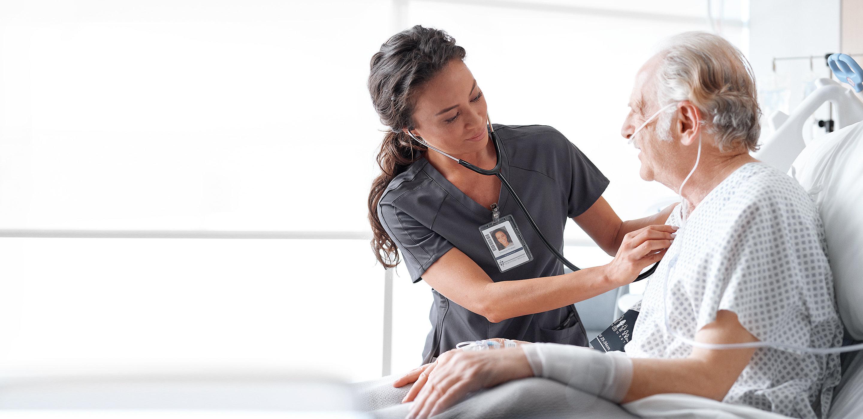 Un patient qui porte une canule nasale se tient assis et droit dans un lit de Hillrom pendant que sa clinicienne écoute son cœur avec un stéthoscope.