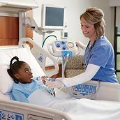 A young patient in a hospital bed receives therapy from the MetaNeb system, with help from her clinician