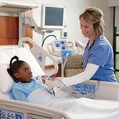 Una paciente joven en una cama de hospital recibe tratamiento del sistema MetaNeb con la ayuda de su médico