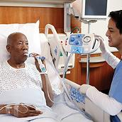 An older patient in a hospital bed receives therapy from the MetaNeb system, his clinician nearby