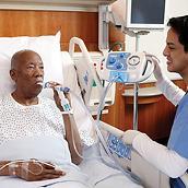 Un paciente más mayor en una cama de hospital recibe tratamiento del sistema MetaNeb con su médico cerca