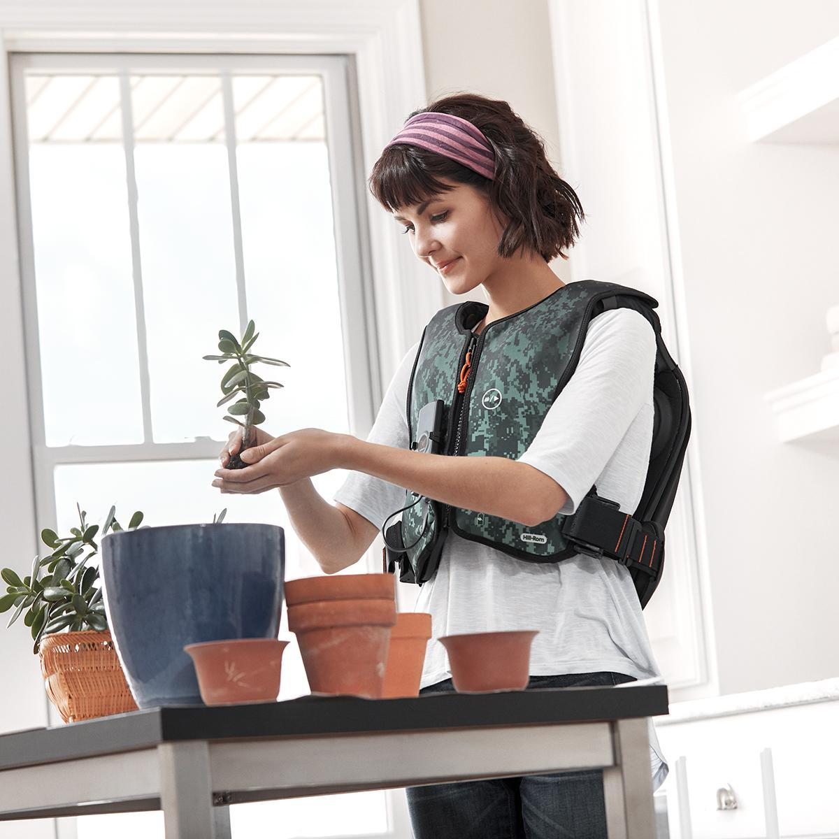 A smiling young woman with black hair, wearing a colorful Monarch® System vest and purple headband, pots plants in her living room.