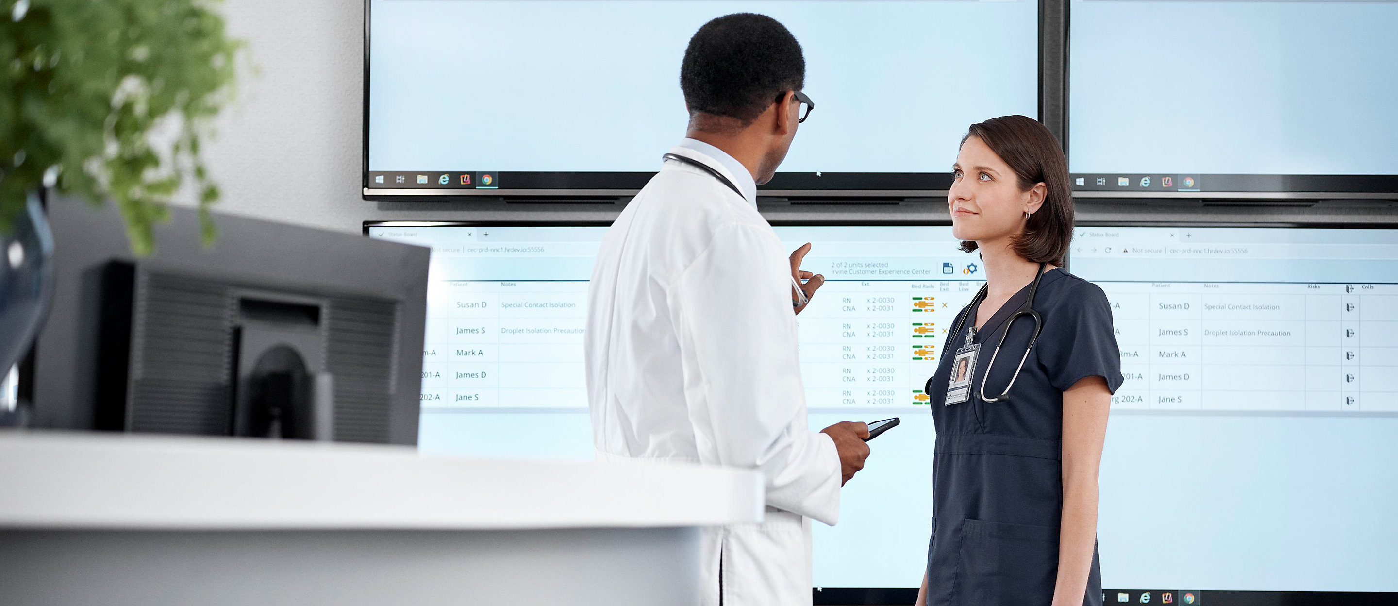 Two clinicians discuss patient statuses near a nurses' station, with large monitors displaying Voalte Nurse Call.
