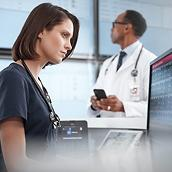 Nurse using Connex Central Station on desktop computer, doctor in background using smartphone