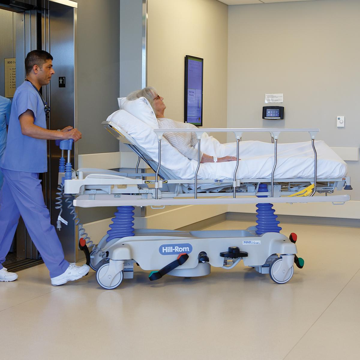 Un médico empuja una camilla para procedimientos de Hillrom llevando a un paciente fuera del ascensor de un hospital.