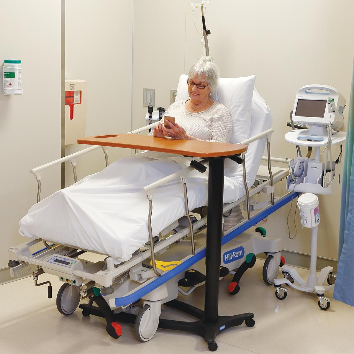 Una paciente usa su teléfono mientras está sentada en posición vertical en una camilla para procedimientos de Hillrom. Apoya las manos sobre una mesa que se encuentra sobre la cama.