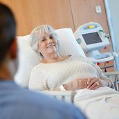 Un especialista clínico se acerca a una paciente sonriente en una camilla para procedimientos de Hillrom. Un monitor de signos vitales Connex® se encuentra en segundo plano.