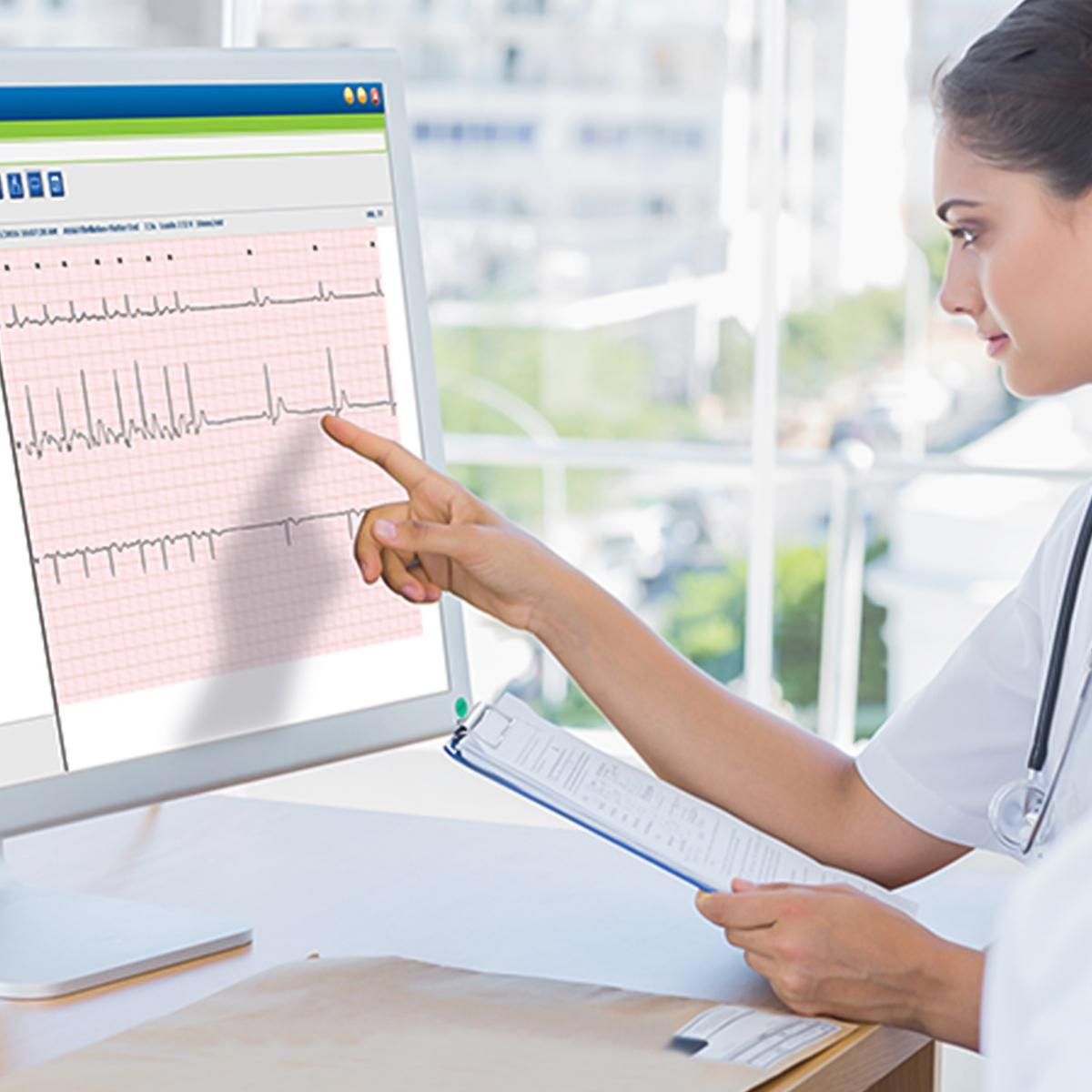 Female clinician pointing to and ECG waveform on a screen