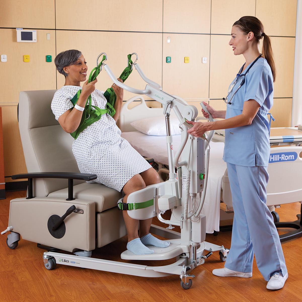 A clinician helps an older female patient stand from a chair using a Sabina II mobile lift