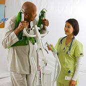 A clinician helps an older male patient stand using a Sabina SafetyVest Lift Aid
