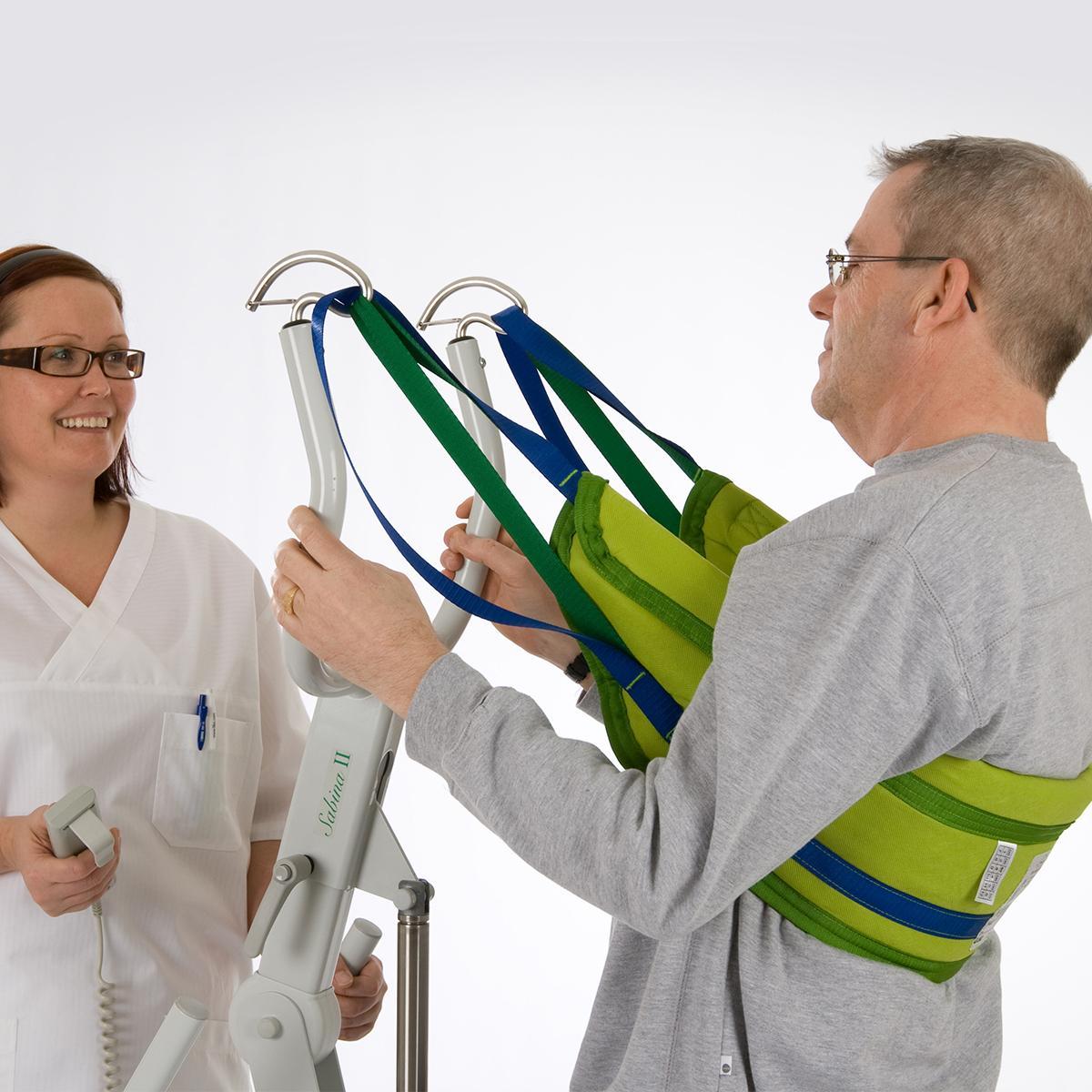 Une clinicienne aide un patient à se tenir debout à l'aide d'un dispositif d'aide au levage Solo SupportVest.