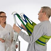 A clinician helps a male patient stand using a Solo SupportVest Lift Aid