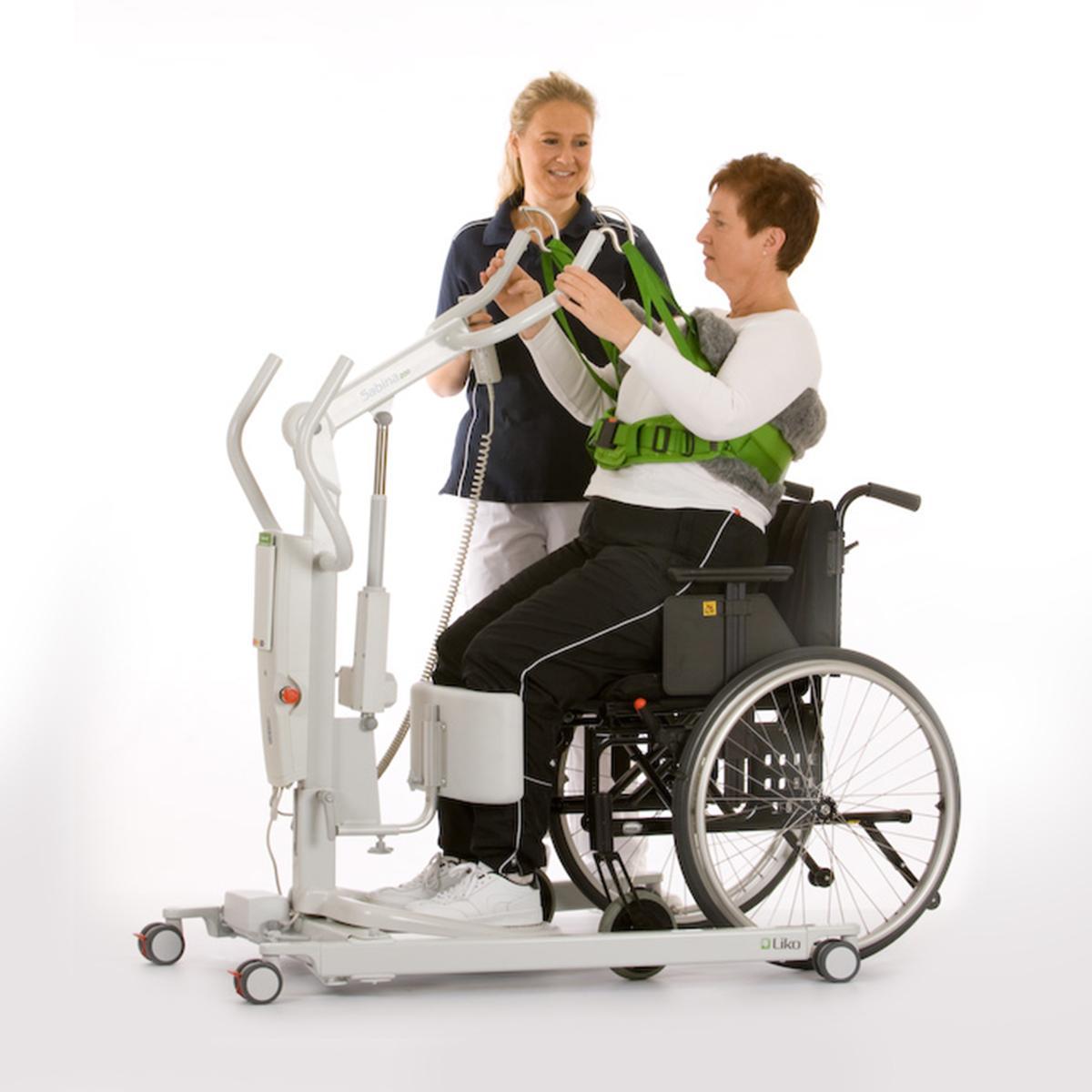 Un clinicien aide une patiente à se lever d'un fauteuil roulant à l'aide d'un dispositif d'aide au levage SupportVest.
